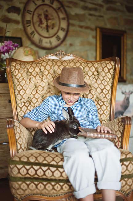 Мальчик сидит с домашним кроликом, держа книгу — стоковое фото