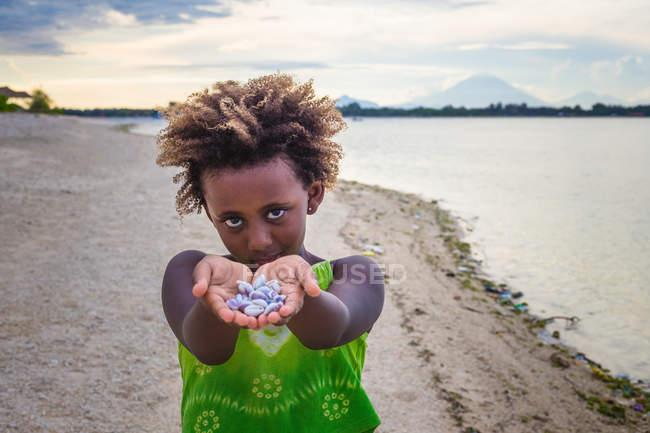 Girl standing on beach and showing seashells, Indonesia — Stock Photo