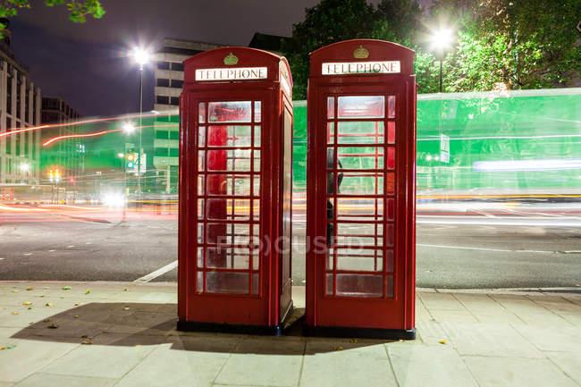 Легкие тропы и красные телефонные будки, Лондон, Англия, Великобритания — стоковое фото