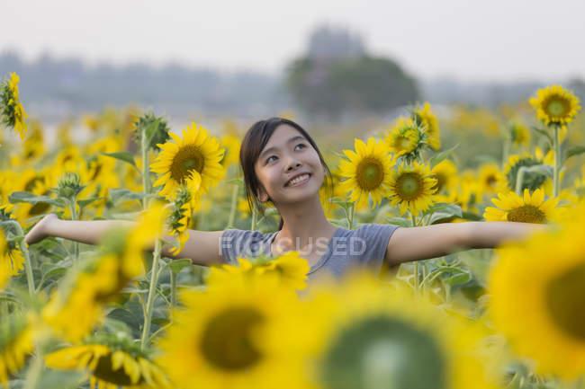 Souriant Adolescente debout dans le champ de tournesols — Photo de stock