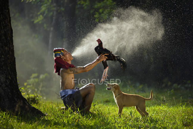Man holding cockerel bird and dog standing on green grass, Asia — Stock Photo