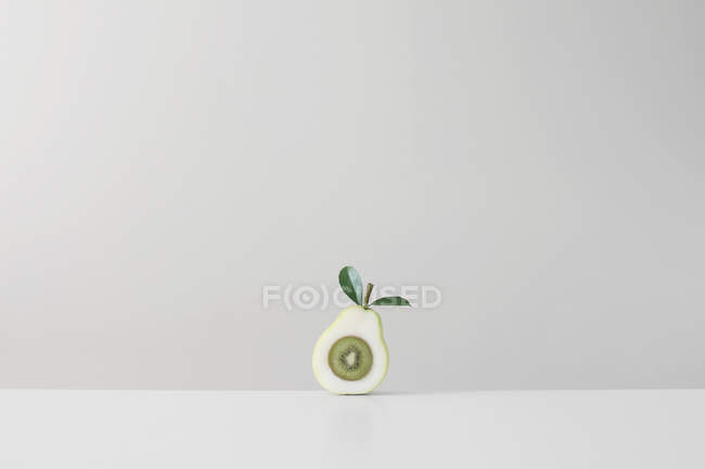 Kiwi fruit inside halved pear against grey wall — Stock Photo