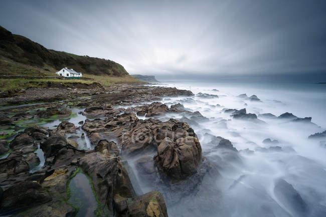 Ирландия, Ballycastle, живописный вид на дом на море и массивные скалы — стоковое фото