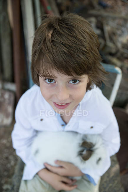 Portrait of Smiling Boy holding fluffy pet rabbit — Stock Photo