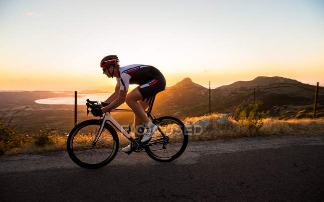 Человек на велосипеде на закате, Корсика, Франция — стоковое фото