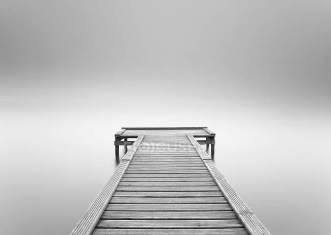 Empty wooden jetty in the mist, monochrome — Stock Photo