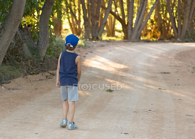 Chico caminando por el camino en el campo — Stock Photo