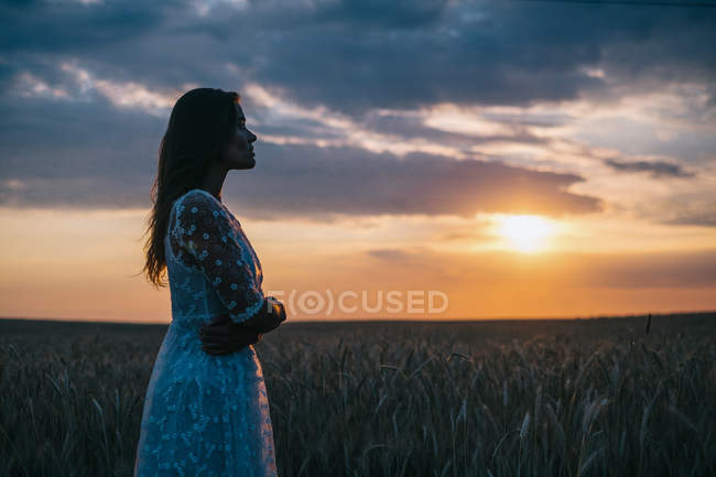 Side view of sensual woman standing in wheat field and looking at sunset — Stock Photo