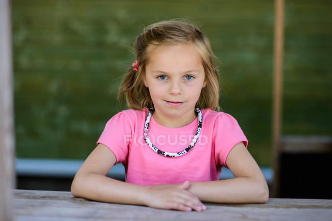 Портрет улыбающейся блондинки, сидящей за столом — стоковое фото