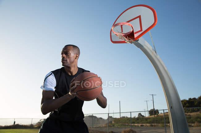 Молодой человек играет в баскетбол в парке — стоковое фото