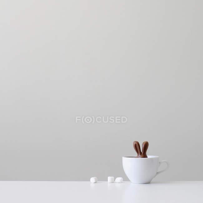 Шоколадный кролик в белой чашке против серой стены — стоковое фото