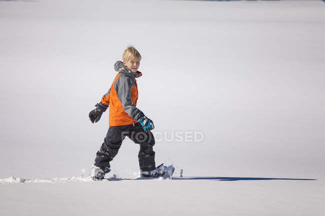 Happy young boy snowshoeing in snow — Stock Photo