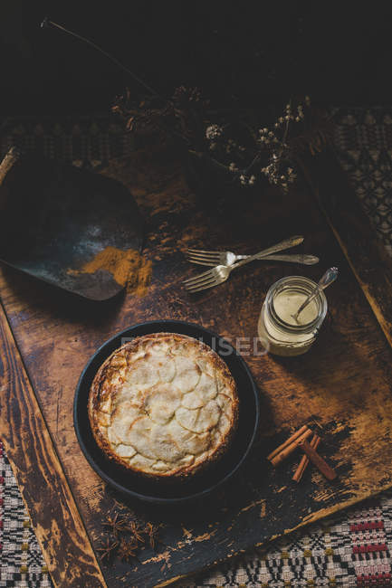 Apple pie on a plate, condensed milk in jar and cinnamon on a shabby wooden tray — Stock Photo