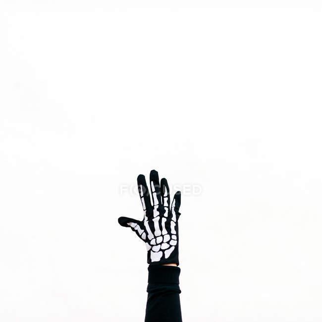 Рука носіння скелет спорядження, розмахуючи на білому тлі — стокове фото