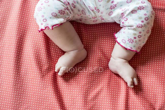 Обрезанное изображение младенца ноги девушка на кровати — стоковое фото