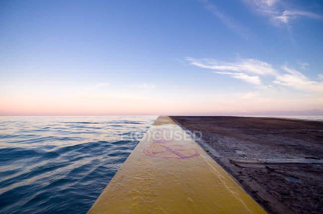 Bord d'une jetée par la mer au lever du soleil, Jamaïque — Photo de stock