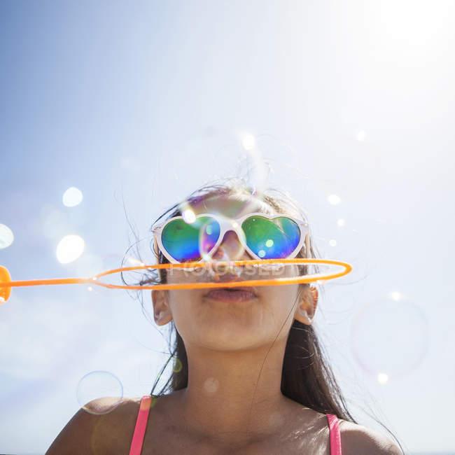 Menina em forma de coração óculos de sol na praia soprando bolhas com varinha de bolha — Fotografia de Stock