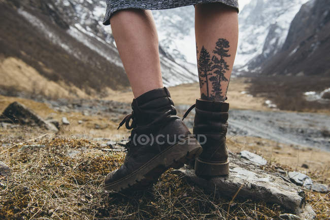 Close-up of tattoo on female leg and walking boots, rear view — Stock Photo