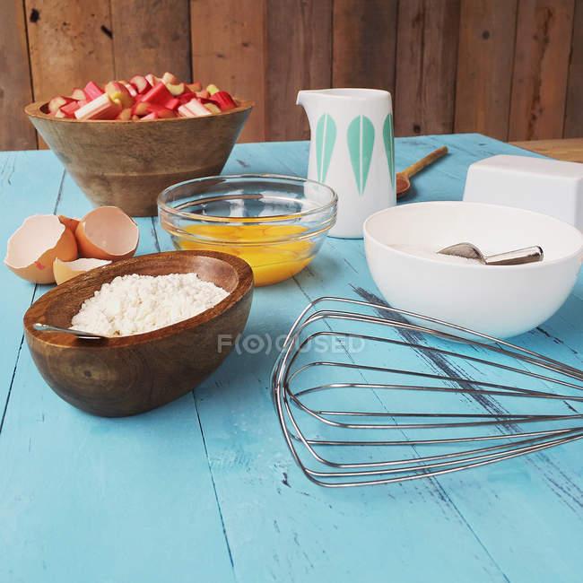 Ingredientes para hornear un pastel de ruibarbo en la mesa azul - foto de stock