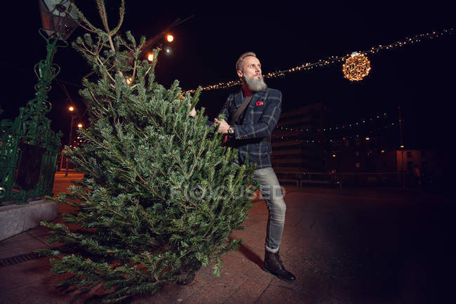 Hipster Man holding a Christmas tree at night — Stock Photo