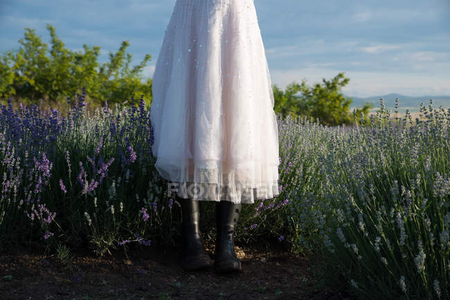 Woman wearing skirt and rubber boots standing in a lavender field — Stock Photo