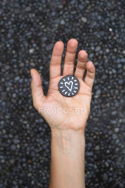 Рука держит сердце окрашены на небольшой камень — стоковое фото