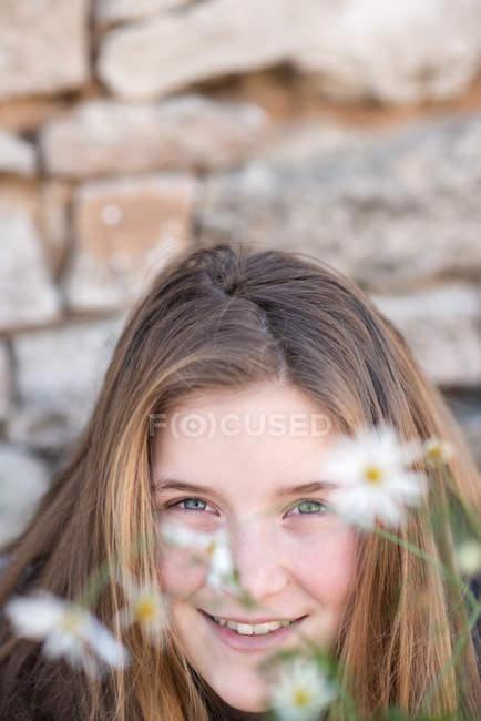 Портрет улыбающаяся девочка с цветами ромашки — стоковое фото