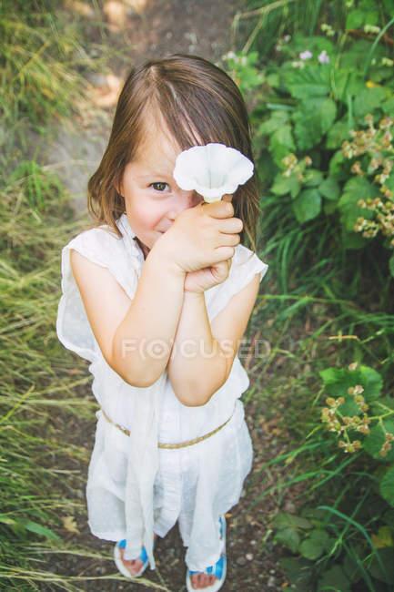 Menina, segurando uma flor na frente entre as plantas — Fotografia de Stock