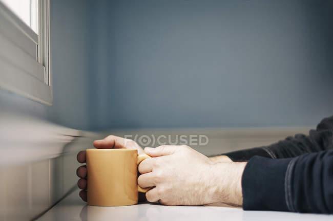 Man holding orange mug of coffee while sitting near window — Stock Photo