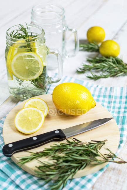 Свежий лимонад с розмарином над деревянным столом — стоковое фото