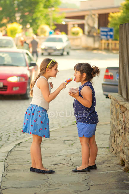Two cute sisters sharing ice cream on city street — Stock Photo