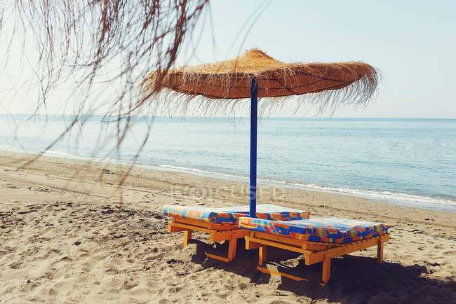 Scenic view of straw parasol and two sun loungers on the beach — Stock Photo