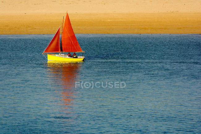 Barca a vela gialla con vele rosse in spiaggia — Foto stock