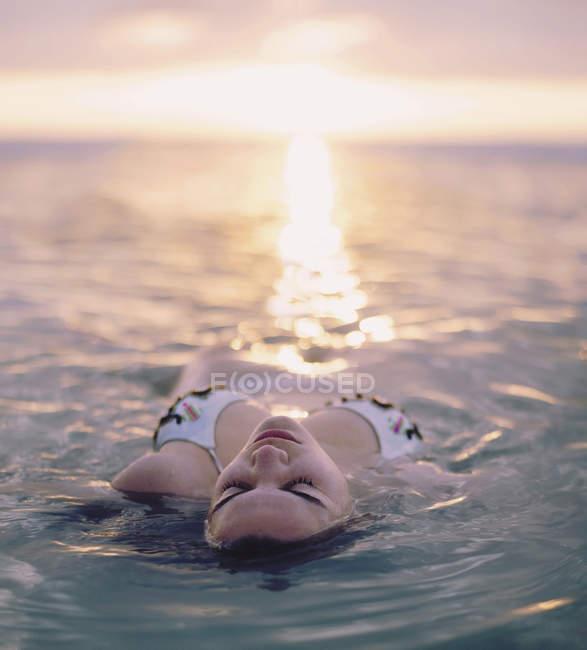 Giovane donna galleggiante in mare al tramonto — Foto stock