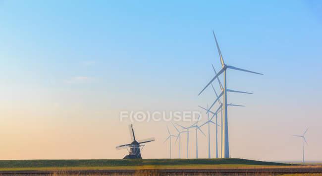 Reihen von Windenergieanlagen und einer alten traditionellen Windmühle, Eemshaven, Groningen, Niederlande — Stockfoto
