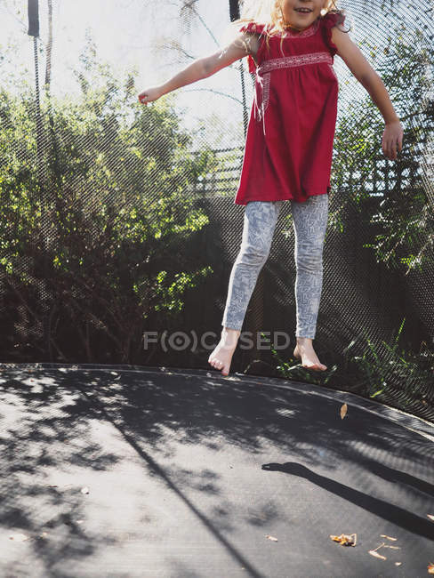 Girl jumping on a trampoline in garden with arms outstretched — Stock Photo