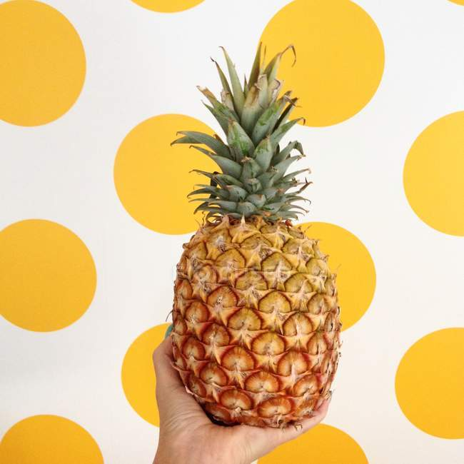 Female hand holding pineapple in front of yellow spot background — Stock Photo