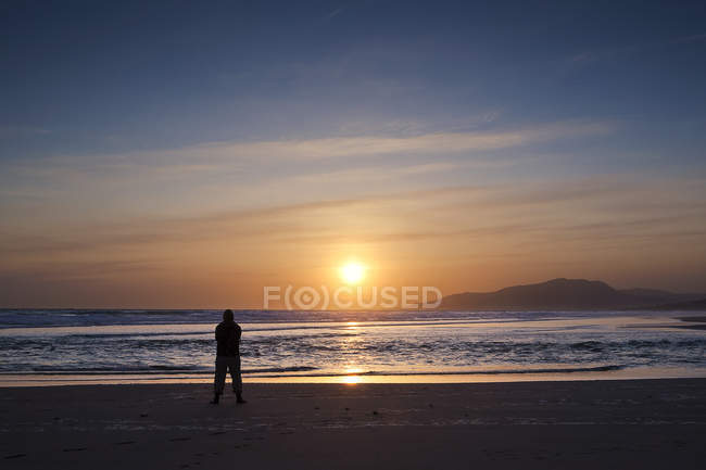 Silhouette of man standing on beach at sunset, Tarifa, Andalucia, Spain — Stock Photo