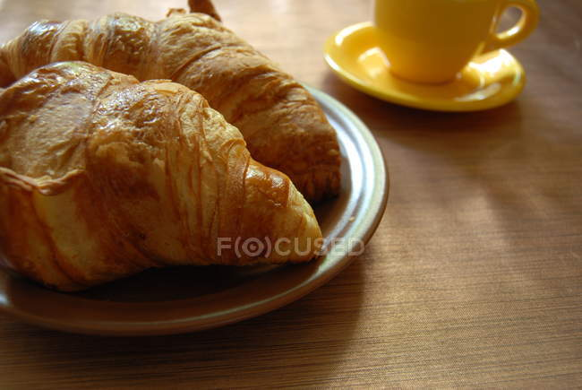 Croissants and cup of coffee over wooden table, closeup — Stock Photo