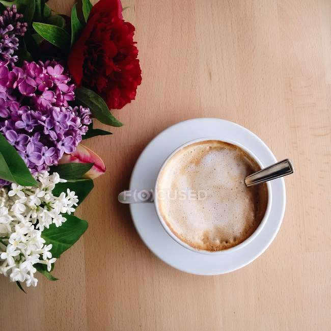 Overhead view of coffee and flowers on table — Stock Photo