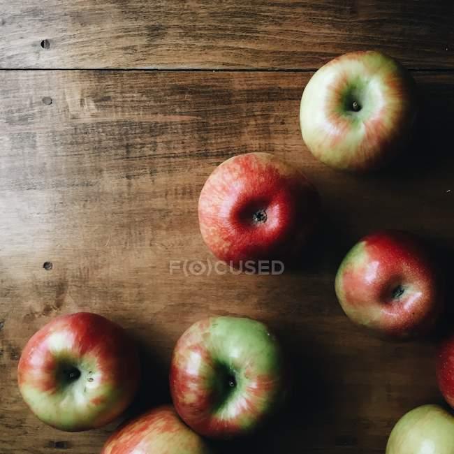Manzanas frescas maduras en una mesa de madera, vista superior - foto de stock