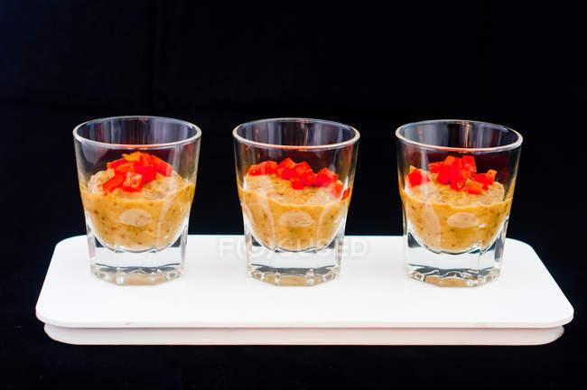 Tre bicchieri di zuppa di verdure fredda con peperoncino tritato — Foto stock