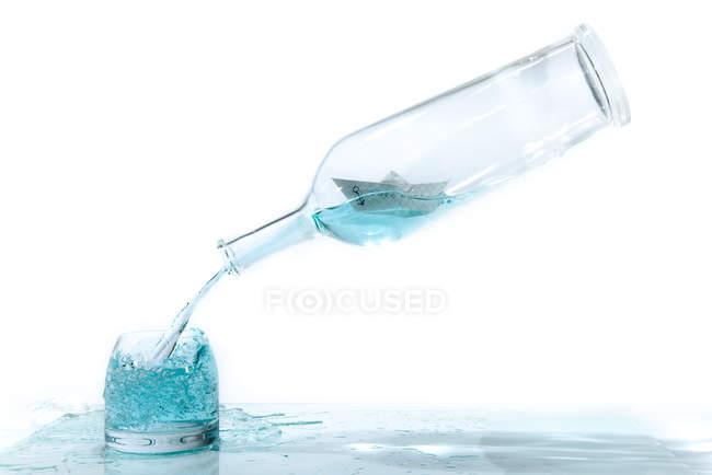Barca di carta in bottiglia di grappa su sfondo bianco — Foto stock