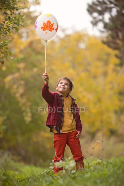 Menino segurando um balão na floresta de outono — Fotografia de Stock