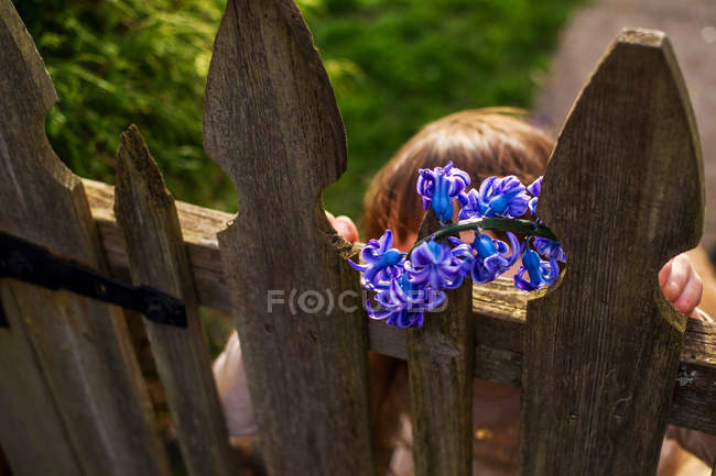 Girl with hyacinth flowers standing behind wooden gate in garden — Stock Photo