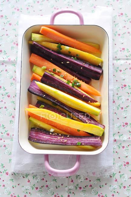 Вид зверху помаранчевий, фіолетовий і жовтий моркву в випічки блюдо — стокове фото