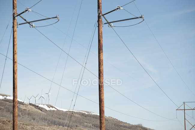 Scenic view of wind turbines juxtaposed with power lines, Wyoming, America, USA — Stock Photo
