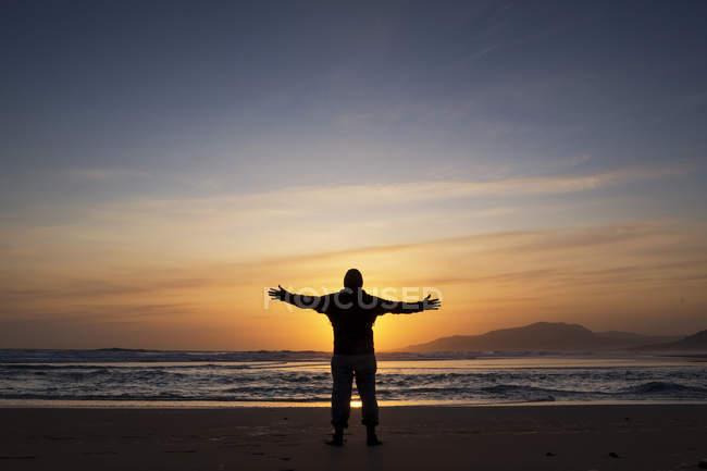 Silueta de hombre de pie con los brazos extendidos en la playa al atardecer, Tarifa, Andalucía, España - foto de stock