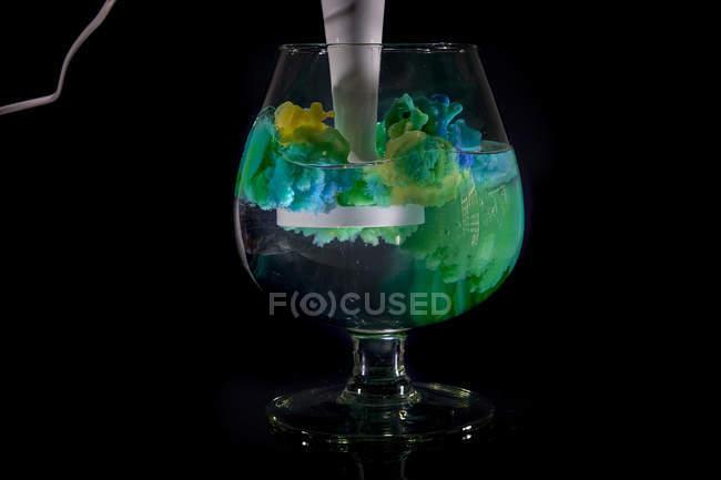Pintura acrílica amarilla y azul mezclada en un vaso de agua - foto de stock