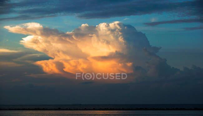 Живописный вид драматических облаков над пляжем на закате — стоковое фото